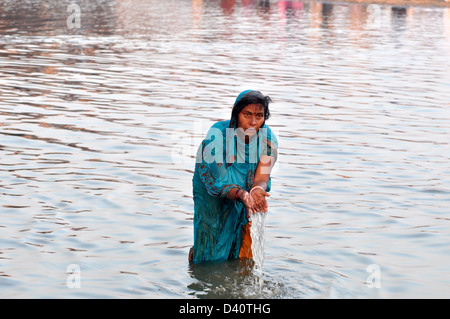 Un indù devoti pregare come stand nelle acque del Sangam o la confluenza del Yamuna, Gange e mitico Saraswati fiumi Foto Stock