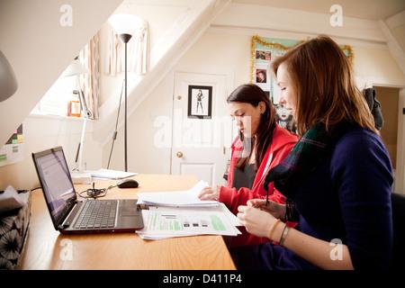 Due donne gli studenti che studiano insieme alla loro scrivania con computer portatile in camera University, Inghilterra, Foto Stock