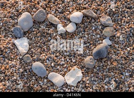 Forma di cuore fatta di ciottoli su una spiaggia Foto Stock