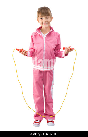 La bambina in una rosa tuta sportiva passa attraverso un salto con la corda Foto Stock