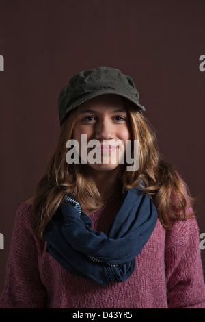 Ritratto di ragazza sorridente alla fotocamera, con berretto da baseball e sciarpa, Studio shot su sfondo nero Foto Stock