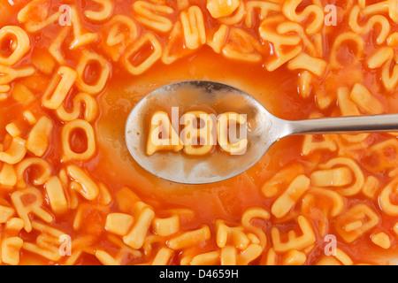 La pasta a forma di lettere ABC su un cucchiaio entro la pasta lettere sagomate in salsa di pomodoro Foto Stock