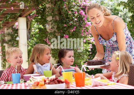 Madre di servire la torta di compleanno con un gruppo di bambini all'aperto Foto Stock