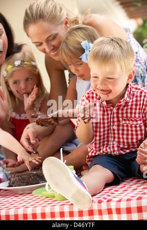 Bambini e madri di mangiare la torta a Outdoor Tea Party Foto Stock