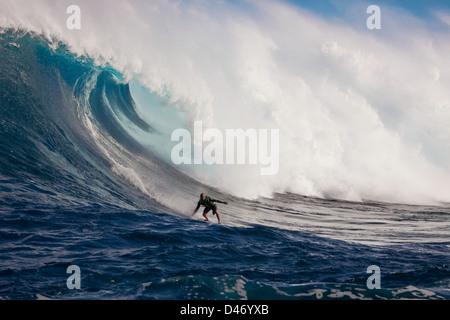 Un tow-in surfer scende giù per la faccia di Hawaii's big surf a Peahi (ganasce) off Maui, Hawaii, Stati Uniti d'America. Foto Stock