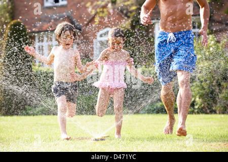 Padre e due figli in esecuzione tramite sprinkler da giardino Foto Stock