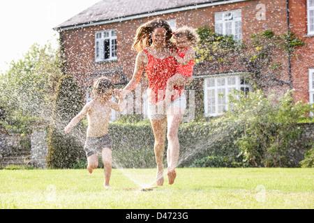 Madre e due figli in esecuzione tramite sprinkler da giardino Foto Stock