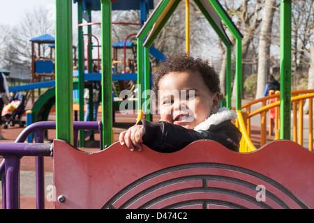 Razza mista toddler baby sorridente e giocando sul telaio di arrampicata in una giornata di sole indossando giacca Foto Stock