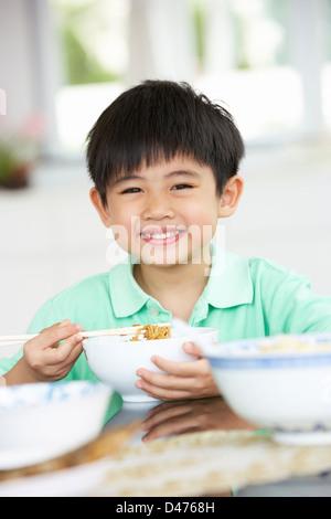 Giovane ragazzo cinese seduti a casa a mangiare pasti