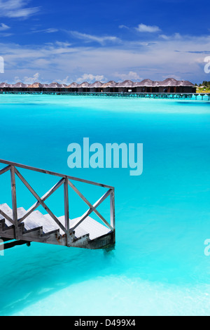 Passi in incredibile laguna blu con bungalow sull'acqua Foto Stock