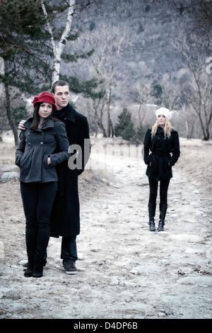 Un giovane sotto braccio e una seconda donna è lasciato alle spalle Foto Stock