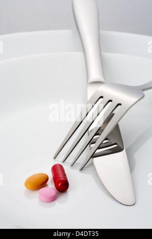 Forcella, coltello e tre pillole su una piastra Foto Stock