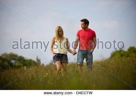 Una giovane coppia camminando mano nella mano attraverso un campo in estate Foto Stock