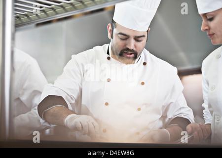 Gli chef cucinare nel ristorante cucina Foto Stock