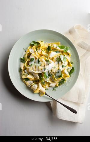 Un piatto di pappardelle con crema di ricotta, baby spinaci erbe fresche e pepe nero. Foto Stock