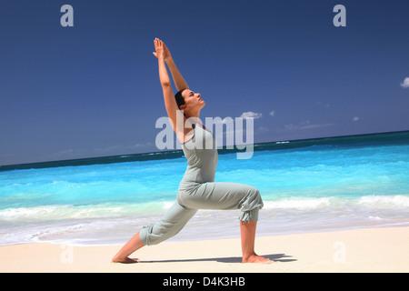 La donna a praticare yoga sulla spiaggia tropicale Foto Stock