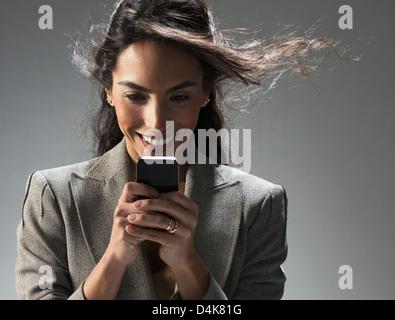 Imprenditrice tramite telefono cellulare Foto Stock