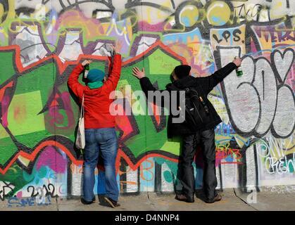 I dimostranti abbraccio la East Side Gallery, un pezzo di arte e di una parte del vecchio Muro di Berlino a Berlino, Foto Stock