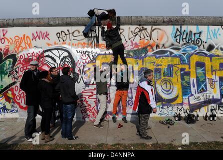 I dimostranti salire la East Side Gallery, un pezzo di arte e di una parte del vecchio Muro di Berlino a Berlino, Foto Stock