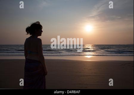 Impostare su Arossim Beach, a sud di Goa, India. Una donna si affaccia al mare come il sole tramonta nel pomeriggio. Foto Stock