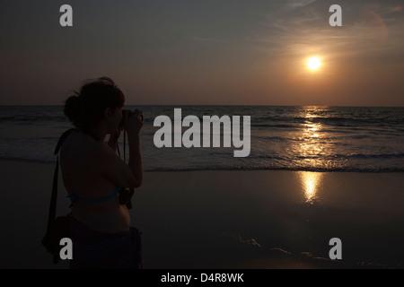 Una femmina di fotografo dilettante a sparare in sun come si imposta sul Mare Arabico. Arossim Beach, a sud di Goa, India. Foto Stock