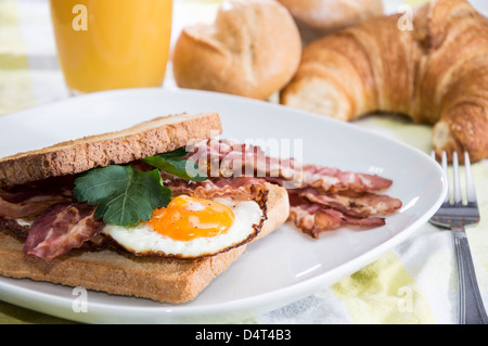 Uovo fritto sandwich con pancetta affumicata su una piastra Foto Stock