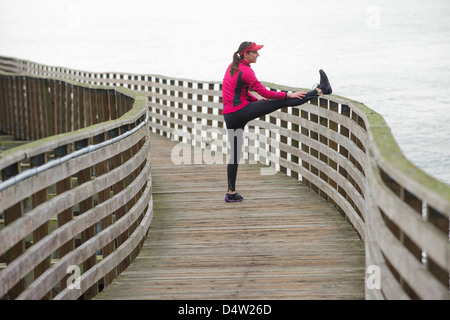 Runner stretching sul dock in legno Foto Stock