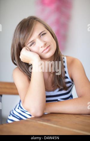 Ragazza adolescente in appoggio la guancia a portata di mano