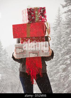 Razza mista donna holding pila di presenta nella neve Foto Stock