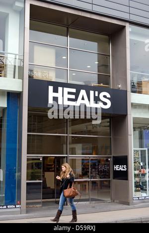 Giovane donna passa un ramo di guarire il negozio di arredamento a Kingston upon Thames Surrey, Inghilterra Foto Stock