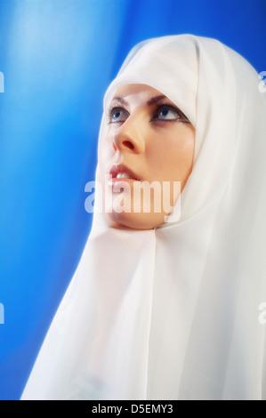 Nun in bianco pregando guarda in alto Foto Stock