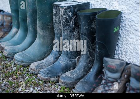 Una fila di verde e nero fangoso stivali da pioggia tutti schierati contro un muro dopo una bella passeggiata in famiglia nella campagna inglese in un agriturismo Foto Stock