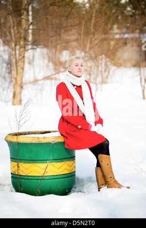 Giovane donna seduta su vuoto grande vaso verniciato Foto Stock