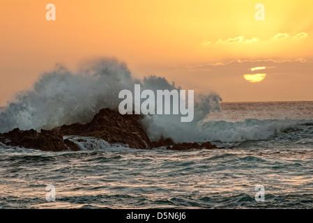Onde che si infrangono sulle rocce al tramonto, Fuerteventura Foto Stock