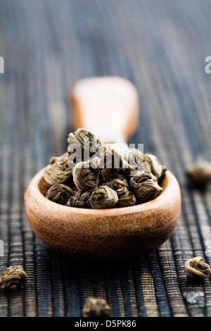 Fresco di foglie di tè verde sul filato in legno Foto Stock