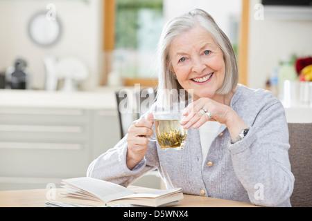 Donna anziana bere il tè e la lettura Foto Stock