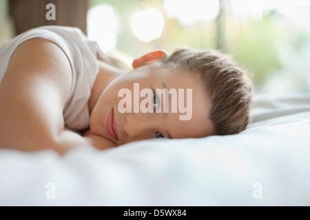 Ragazza sorridente posa sul letto Foto Stock