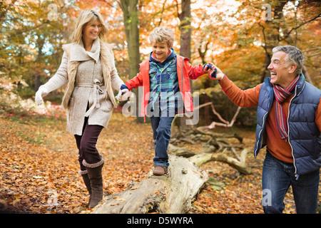 Famiglia camminando sul log in posizione di parcheggio Foto Stock