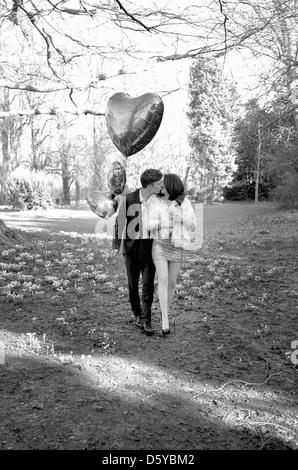 Coppia giovane baciare in Park di contenimento a forma di cuore palloncini Foto Stock