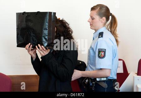 Il convenuto che si nasconde dietro un sacco prima il processo presso il tribunale regionale di Detmold, in Germania, Foto Stock