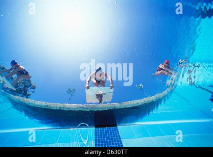 Bassa ngle vista di nuotatori femmina pronto tuffo in piscina dalla posizione di partenza Foto Stock