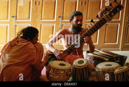 Un monaco indù ( 'sadhu') è la riproduzione di sitar mentre un novizio è in ascolto. Entrambe appartengono alla Foto Stock