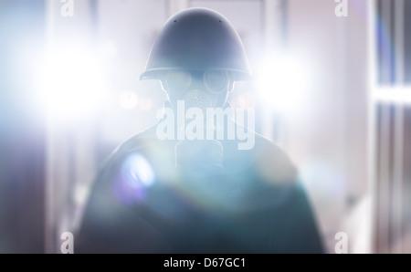 Un uomo nel casco militare e maschera a gas Foto Stock