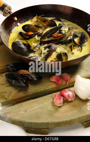 Cozze con cremosa salsa di aglio in una padella bulbo di aglio e chiodi di garofano Foto Stock