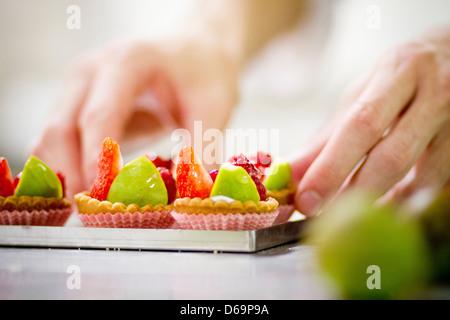 Baker rendendo crostate di frutta in cucina