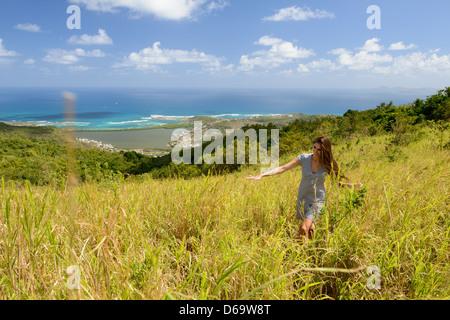 Donna che cammina in un campo di erba alta Foto Stock
