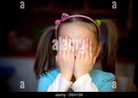 Una bambina di cinque anni si siede al tavolo dei suoi genitori home e nasconde il suo volto in Sieversdorf, Germania, Foto Stock
