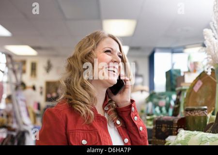 Donna al telefono cellulare in parsimonia store Foto Stock