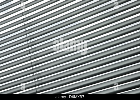 Semi-chiuso persiane metalliche su una finestra, diagonale pattern a strisce. Foto Stock