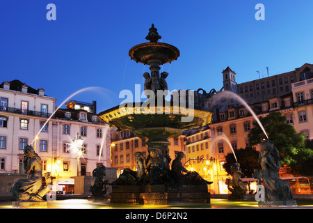 Fontana illuminata di notte, Piazza Rossio (Praca do Dom Pedro IV), nel quartiere di Baixa di Lisbona, Portogallo, Foto Stock